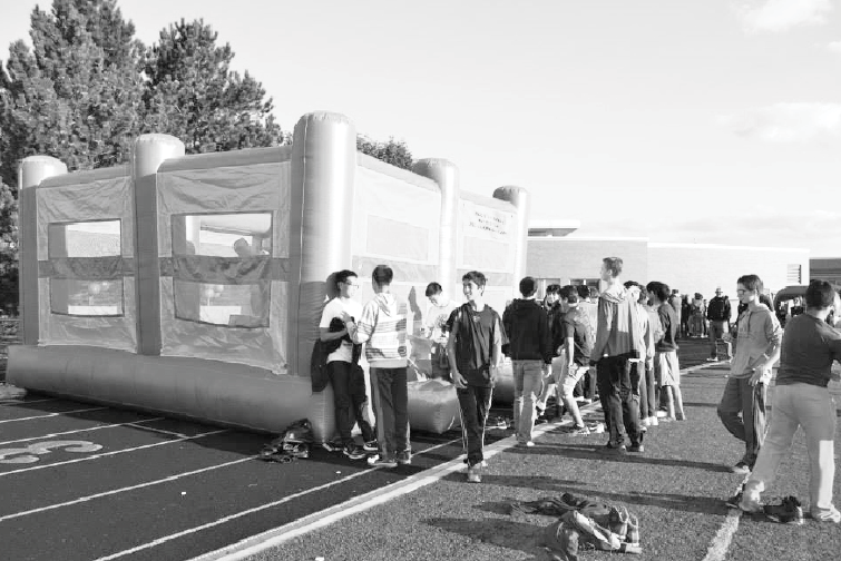 Students get in line outside inflatables set up on the football field for Spirit Fest.