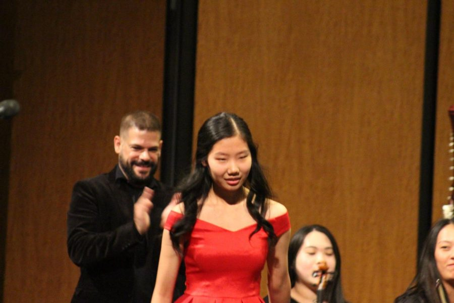 Senior Soloist Stephanie Li '19 walks up to the piano before her solo as Enrique Vilaseco cheers her on. Li went on to perform Ravel's Piano Concerto in G Major, Movement No. 1.