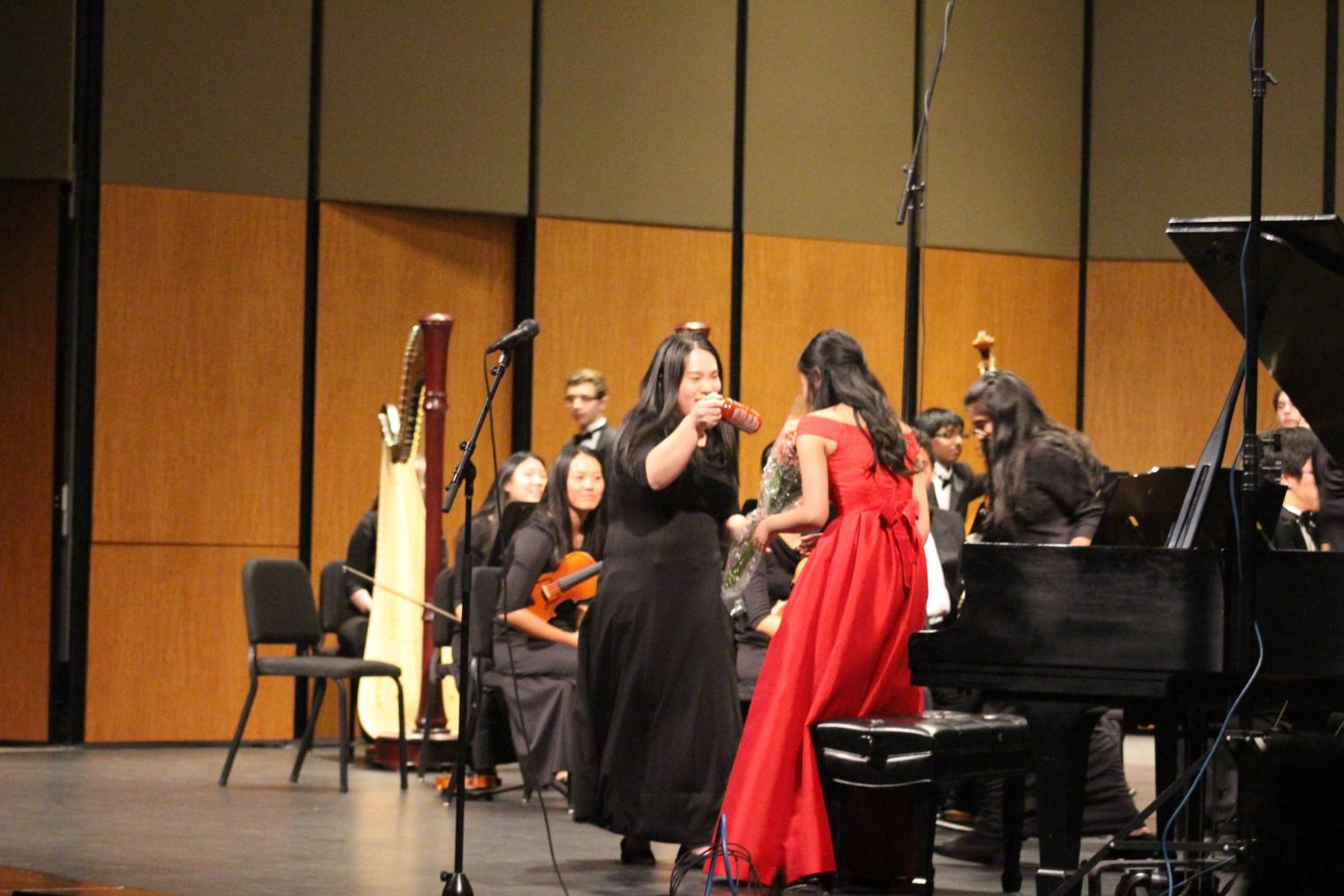Julie Zhu '19 presents Stephanie Li '19 with a bottle of Sriracha. Li was the senior soloist for the concert.