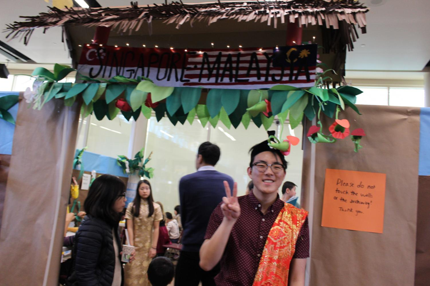 Dylan Chae '20, President of Diversity Council, posed by the entrance to the Singapore and Malaysian booths.  Chae is dressed in traditional Malay clothing.