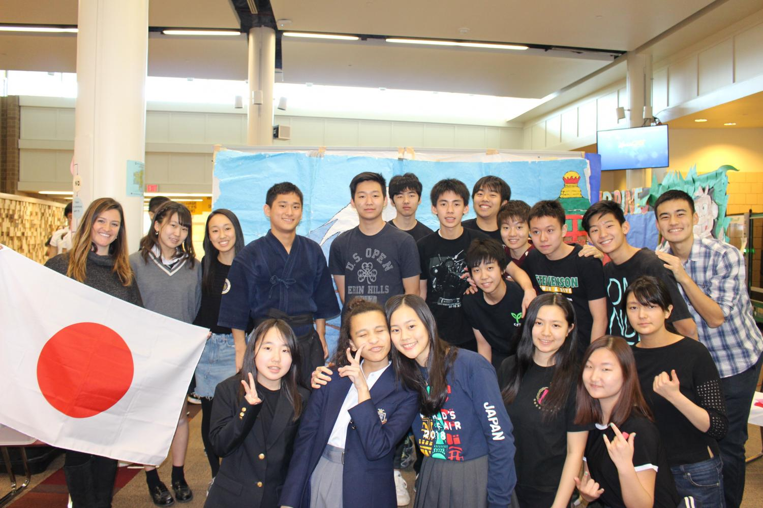 """Rei Kubota '20, Japanese club president, poses with his fellow club members and sponsor.  Later, during the performances, the group showcased a traditional folk dance called """"Soran."""""""
