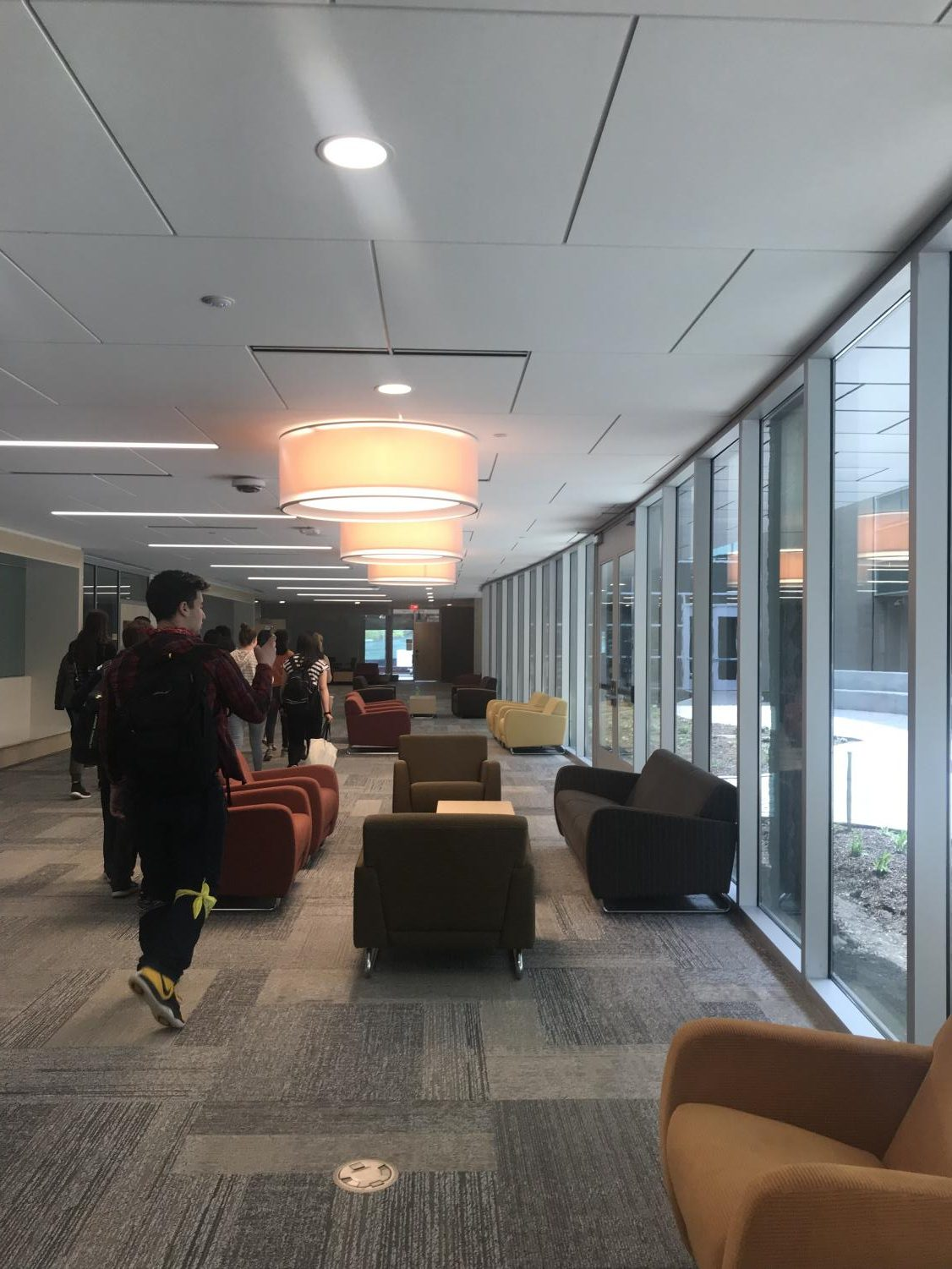 Larger hallways in the new addition are equipped with furniture for student seating between classes. The hallway looks out into the first school courtyard open for student use.