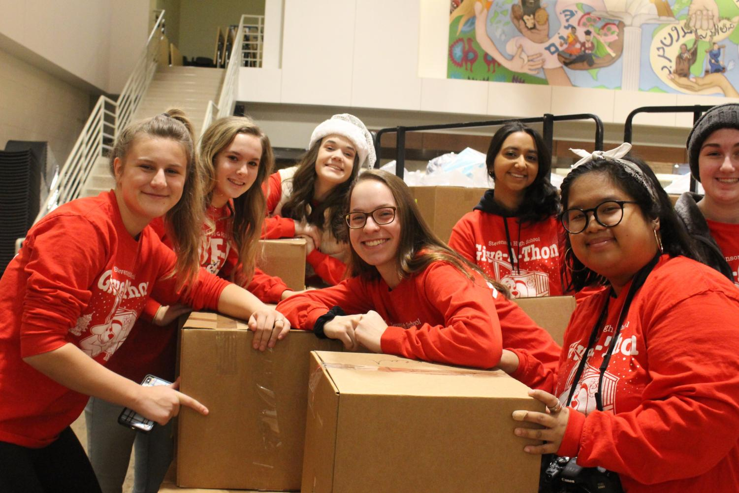 Students pose among food boxes before loading them onto a truck. Ninety-Five volunteers gathered in the Wood Commons to help deliver the gifts bought by many classroom leaders around the school.
