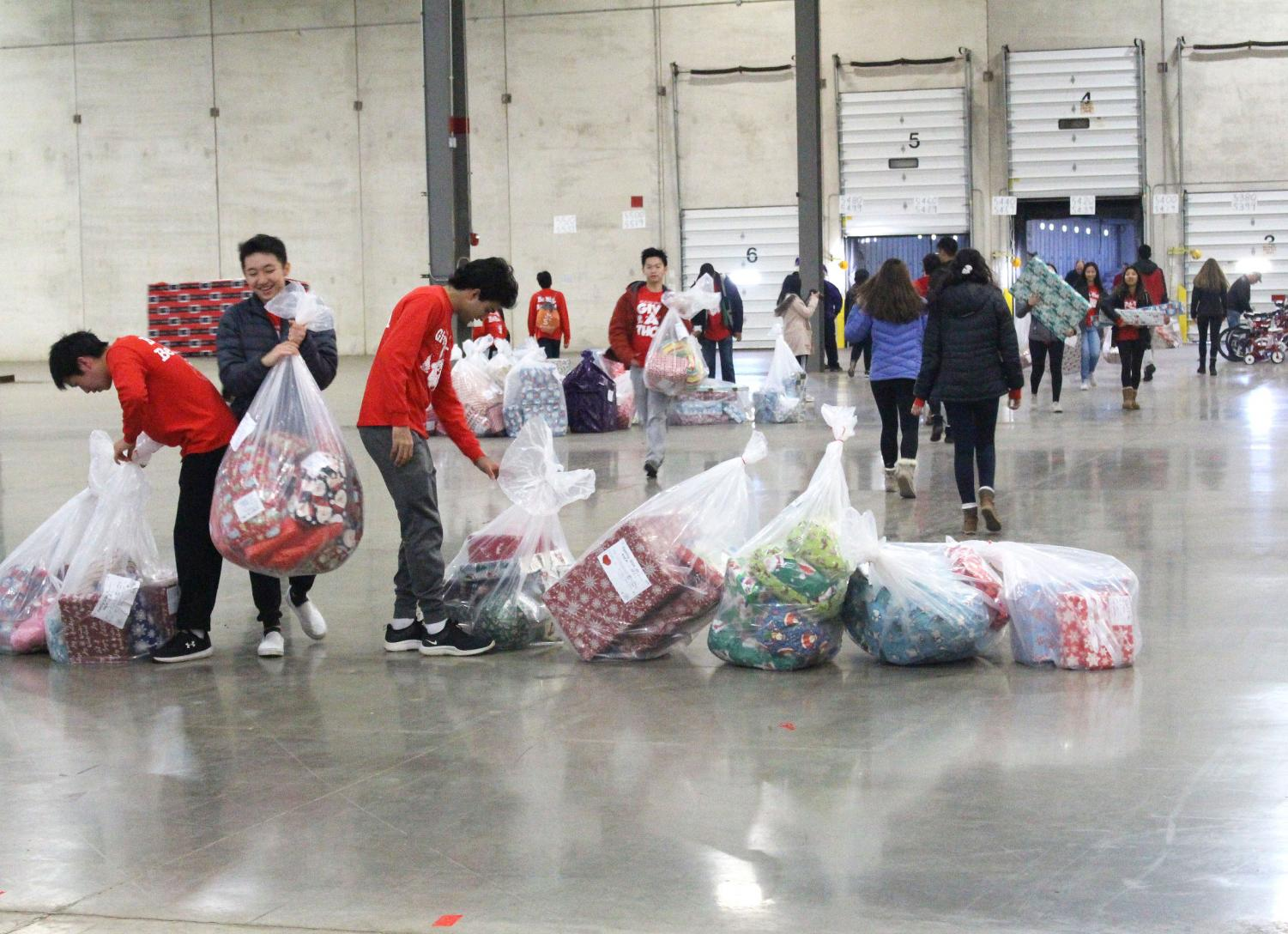 Volunteers line up bags of labeled gifts. Catholic Charities warehouse receives gifts from multiple families and organizations in Lake County to be donated to low income families in the area.