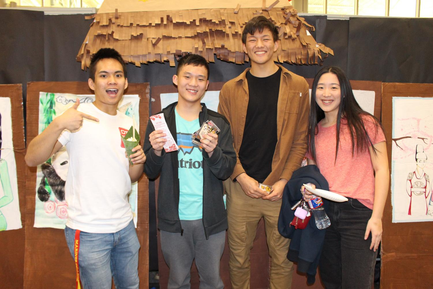 Patrick Tong '20, Connie Song '20, Gavin Meng '20 and Sean De Asis '20 smile in front of the art displays.