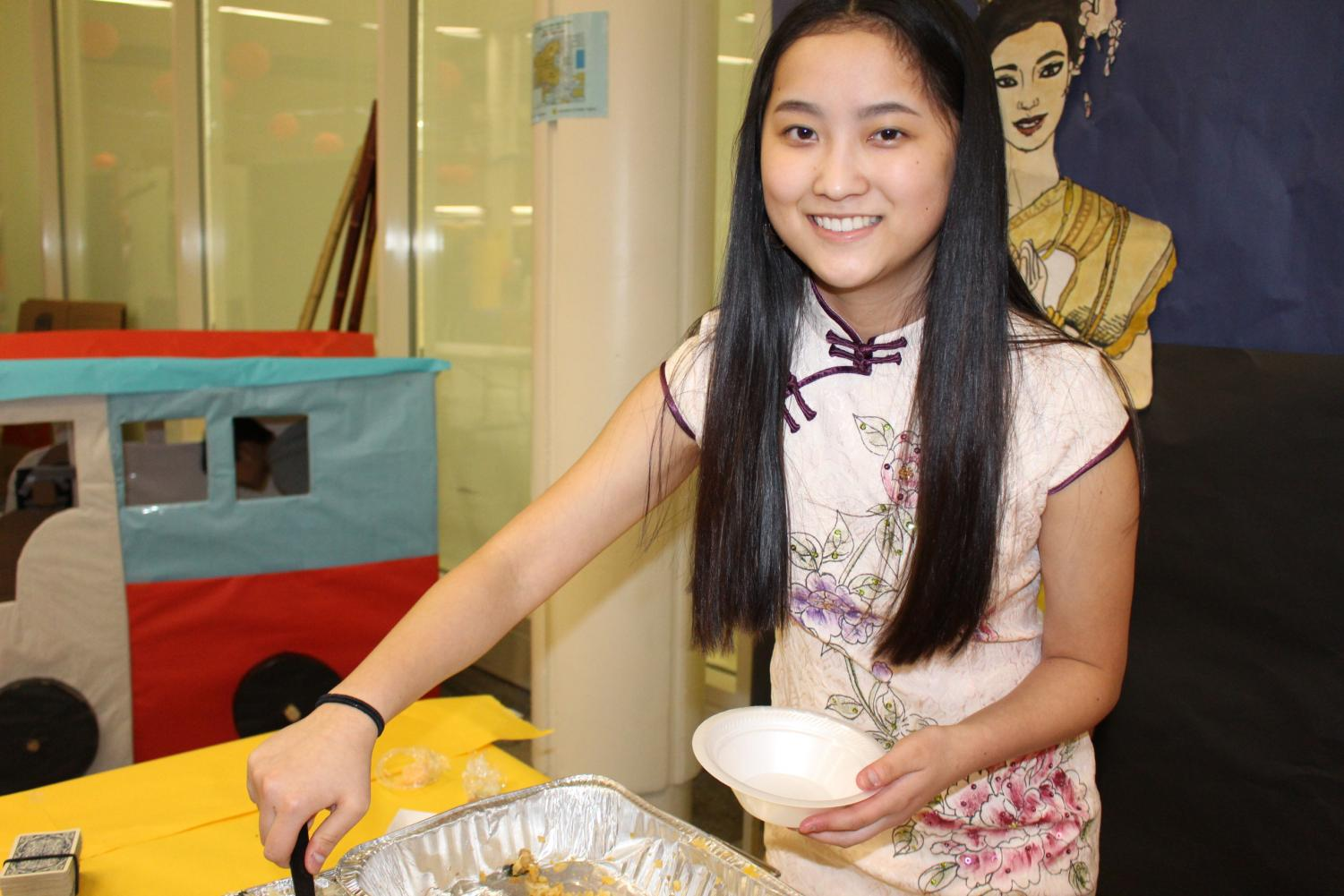 Audrey Smart '21 serve food at the Vietnam booth.