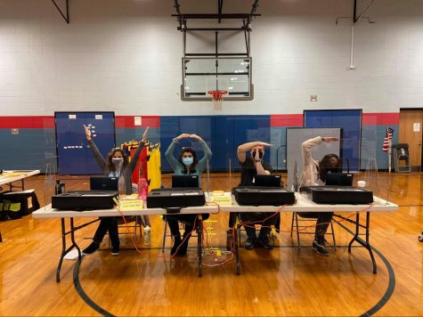 Mikayla Varghese '21 (far right) and other election judges show their enthusiasm on the job. Even though their job lasts many hours on Election Day, election judges are excited to take on the challenge. Courtesy of Varghese.