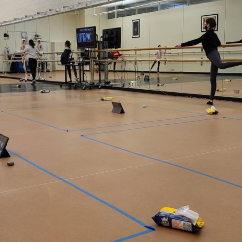 Several containers of wipes are strewn across the floor of a studio for a second period Dance 2 class preparing for their lesson. Students warm up while socially distanced with six foot restrictions taped to the ground to guide the, and reduce the risk of viral transmission. (Photo from Mr. Grice, Director of Fine Arts)